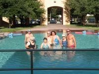 group of seven adults in pool facing camera